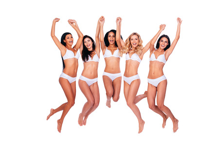 Beautiful breasts: Flying beauties. Full length of five beautiful women in lingerie jumping and keeping arms raised against white background