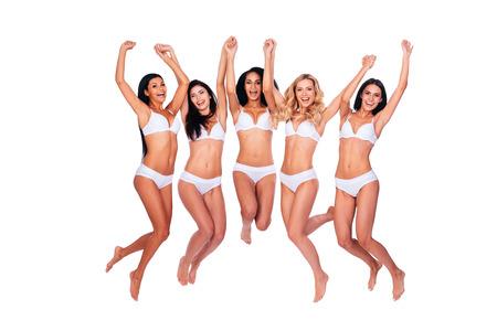 beaux seins: Voler beautés. Longueur de cinq belles femmes en lingerie saut et bras de maintien soulevé contre un fond blanc