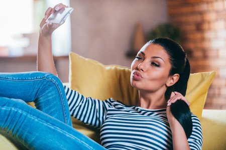 making a face: Selfie time. Beautiful young woman making selfie by her smart phone and making a face while sitting on the couch at home Stock Photo