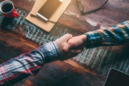 Fechar um acordo. Close-up vista superior de dois homens apertando as mãos sobre a mesa de madeira rústica