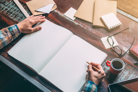 writing desk: Start planning today. Close-up top view image of man writing in notebook with copy space while sitting at the rustic wooden table Stock Photo