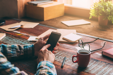 work table: Open for communication. Close-up image of man holding smart phone while sitting at the rustic wooden table