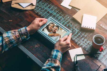 memories: Good memories. Close-up top view image of man holding picture frame while sitting at the rustic wooden table