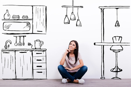 kitchen: Dreaming about new kitchen. Cheerful young woman smiling while sitting on the floor against white background with drawn kitchen