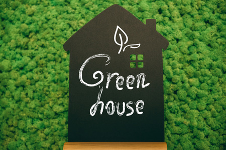 short phrase: Green house. Close-up of house shaped blackboard with hand writing text at moss background