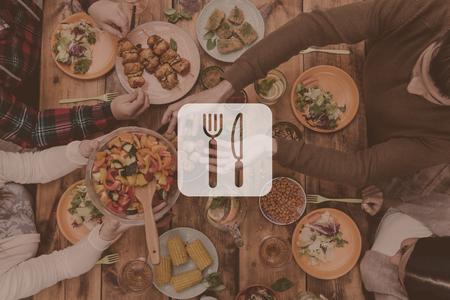 완벽한 저녁 식사. 소박한 나무 테이블에 앉아있는 동안 저녁 식사를 함께하는 4 명의 사람들의 상위 뷰 위에 부엌기구의 디지털 구성된 그림