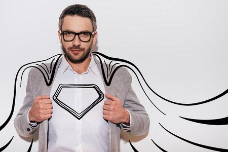Als een held. Zelfverzekerde jonge man aanpassing van zijn jas en op zoek als superheld in zijn getrokken cape tijdens het staan tegen een witte achtergrond Stockfoto