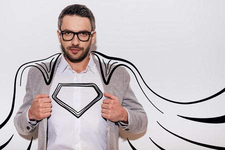Like a hero. Confident young man adjusting his jacket and looking like superhero in his drawn cape while standing against white background