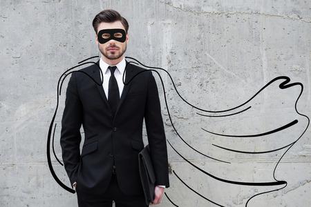 Herói em seu negócio. Homem de negócios novo confiável que desgasta uma capa desenhada e máscara enquanto pé contra a parede de concreto
