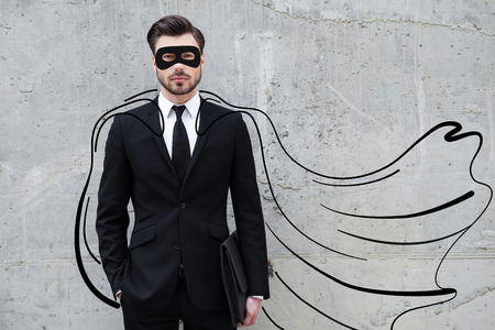 Hero in his business. Confident young businessman wearing a drawn cape and mask while standing against concrete wall