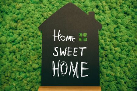 short phrase: Home sweet home. Close-up of house shaped blackboard with hand writing text at moss background