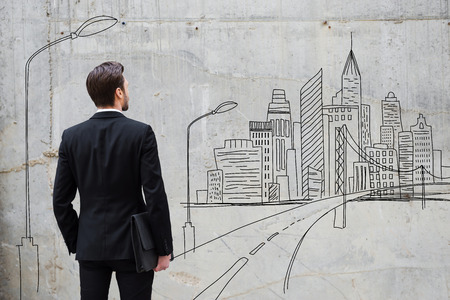 rear view: Moving forward. Rear view of young businessman standing against concrete wall with city sketch on it Stock Photo