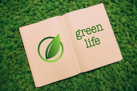 green life: Green life. Top view close-up image of notebook with leaf symbol and text at moss background