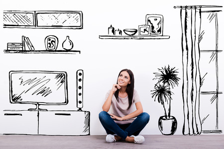 apartment interior: Dreaming about new apartment. Cheerful young woman smiling while sitting on the floor against white background with drawn home interior