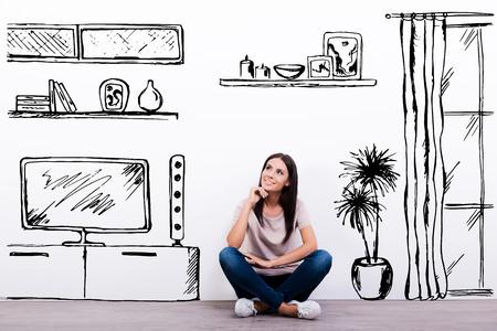 Rêver nouvel appartement. Enthousiaste jeune femme en souriant alors qu'il était assis sur le sol contre un fond blanc avec un intérieur de maison dessinée