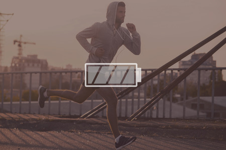 energy symbol: Full energy. Digitally composed picture of full charged battery symbol over picture of the jogger Stock Photo