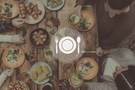 getting together: Getting together for dinner. Digitally composed picture of kitchen utensil over top view of four people having dinner together while sitting at the rustic wooden table Stock Photo