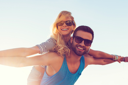 Lovely airplane. Low angle view of smiling young man piggybacking his girlfriend while keeping arms outstretched