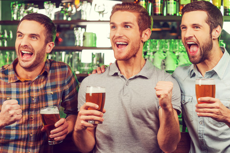 drinks after work: This is a goal! Three happy young men in casual wear holding glasses with beer and gesturing while standing at the bar counter and looking away