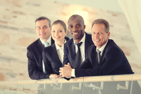 four people: Successful business team. Four confident business people standing close to each other and smiling at camera