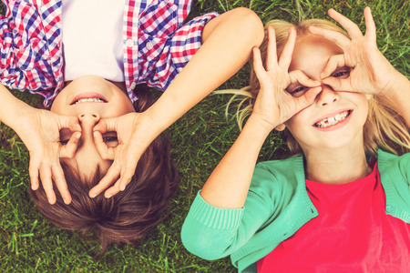 Summer time fun. Top view of two cute little children making faces and smiling while lying on the green grass together