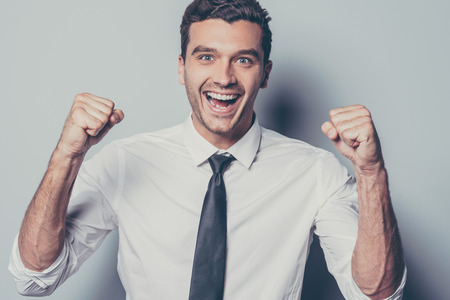 facial expression: Happy winner. Cheerful young man gesturing and keeping his mouth open while standing against grey background Stock Photo