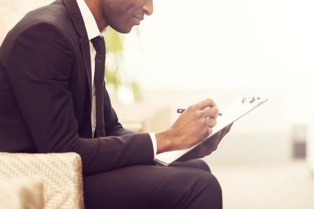 hombre escribiendo: Haciendo algunas notas de negocio. Vista lateral cerca de la imagen de la alegre negocios africano joven escribiendo algo en su bloc de notas y sonriendo mientras está sentado en la silla