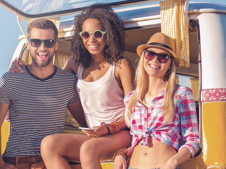 minivan: Spending great time together. Three happy young people bonding to each other and smiling while leaning at the trunk of their retro minivan Stock Photo