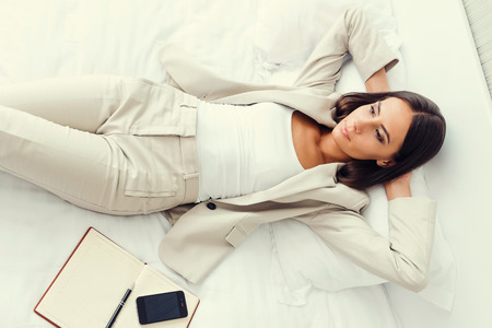 keeping room: She need a break. Top view of beautiful young businesswoman in suit holding hands behind head and keeping  while lying in bed at the hotel room