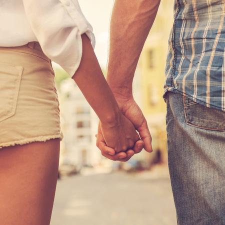ロマンス: 手と心を一緒に。屋外を歩きながら手を繋いでいるカップルを愛するのクローズ アップ