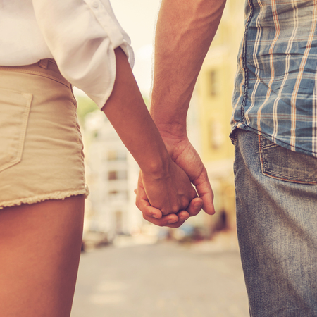 parejas: Las manos y los corazones juntos. Primer plano de la pareja de enamorados de la mano mientras caminan al aire libre Foto de archivo