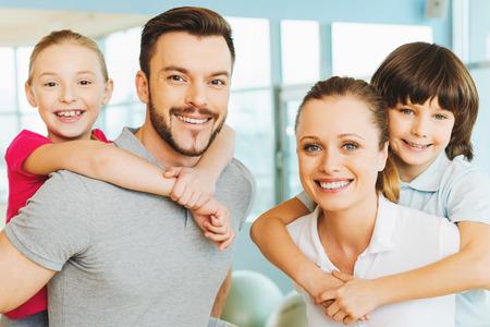 Samenleven gezond leven. Gelukkig sportieve familie bonding elkaar staande in sportclub samen
