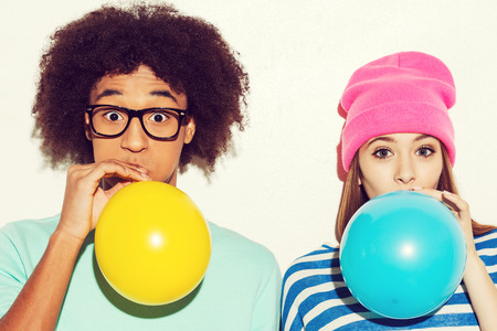 inflating: Living bright lives. Funky young couple inflating balloons while standing against white background Stock Photo