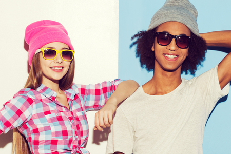 Funky couple. Funky young couple wearing sunglasses and smiling while standing against colorful background