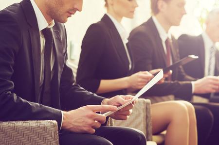 Candidatos de trabajo. Imagen recortada de personas en ropa formal que esperan en línea mientras estaba sentado en las sillas y la celebración de los documentos en sus manos Foto de archivo