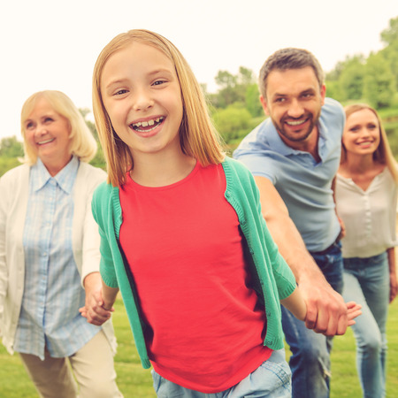 out of focus: Spending great time with family. Happy little girl enjoying time with her family while walking outdoors together Stock Photo