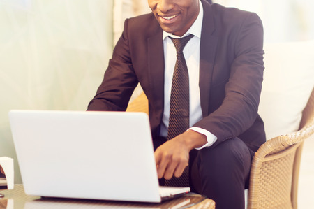 african business man: Working with pleasure. Cropped image of handsome young African businessman using his laptop and smiling
