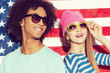 American style. Funky young couple wearing sunglasses and smiling while standing against American flag 版權商用圖片