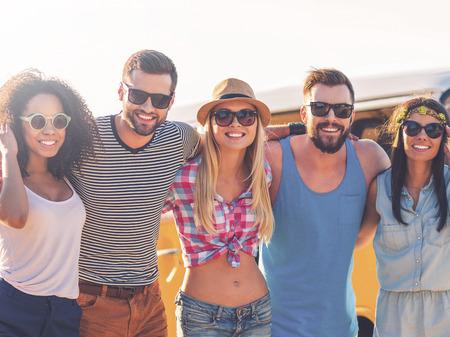 grupo de personas: Joven y despreocupada. Grupo de jóvenes alegres que abrazan y que miran la cámara mientras está de pie en la playa con minivan retro en el fondo