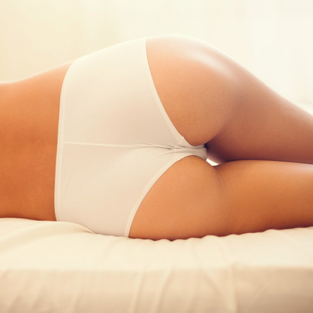 nude female buttocks: Perfect buttocks. Close-up of beautiful young woman with perfect buttocks lying on bed