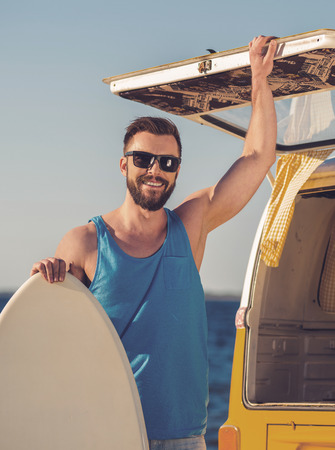 car trunk: Ready to summer! Smiling young man leaning at the skimboard and holding hand on door of car trunk