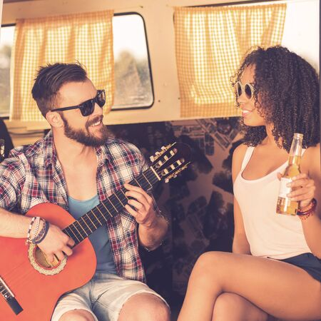 minivan: Enjoying time together. Cheerful young beard man sitting in retro minivan and playing guitar while beautiful young African woman looking at him and smiling Stock Photo