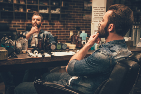 clothing shop: Looking good. Side view of handsome young bearded man looking at his reflection in the mirror and keeping hand on chin while sitting in chair at barbershop