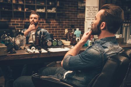 Parece bom. Vista lateral do homem de barba jovem e bonito olhar para o seu reflexo no espelho e manter a mão no queixo enquanto está sentado na cadeira em barbearia