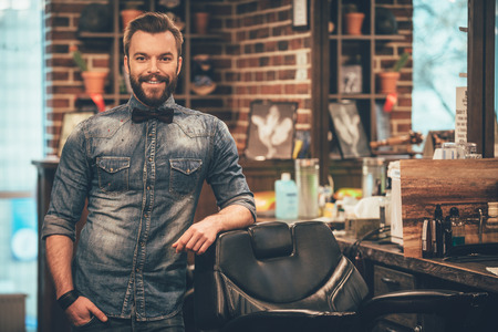 male hair: Barbershop owner. Cheerful young bearded man looking at camera and holding hand in pocket while leaning on chair at barbershop Stock Photo