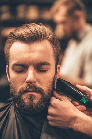 Real man grooming. Close-up of handsome man getting beard haircut by hairdresser at barbershop Imagens