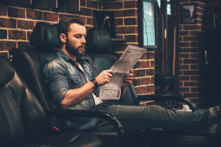 newspaper read: Waiting for appointment. Handsome young bearded man reading newspaper while sitting in comfortable chair at barbershop