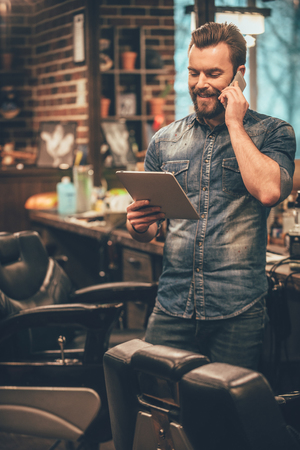 hablando por celular: la cita es el lunes! hombre barbudo joven alegre hablando por teléfono móvil y mirando a la tableta digital mientras está de pie en la peluquería Foto de archivo