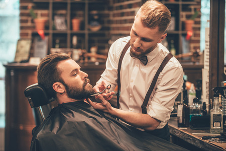 man haircut: Beard grooming. Side view of young bearded man getting beard haircut by hairdresser while sitting in chair at barbershop