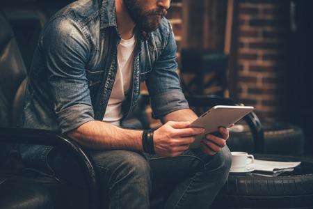 検索では新しいアイデア。デジタル タブレットを保持して椅子に座っている若いのひげを生やした男のクローズ アップ